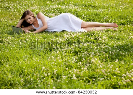woman wearing white dress laying on grass in park with netbook - stock photo