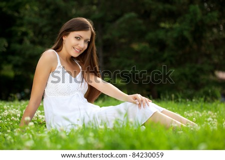 woman wearing white dress sitting on grass in park