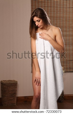 Woman wearing white towel in bathroom - stock photo