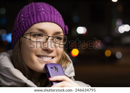 Woman wearing winter clothes using smart phone in the city by night  - stock photo