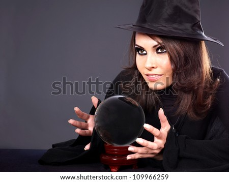 Woman wearing witch hat with crystal ball. Fortune telling. - stock photo
