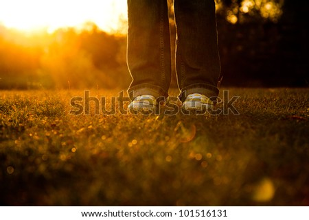 Woman wearing yellow basketball shoes with the suns rays shinning on ground. - stock photo