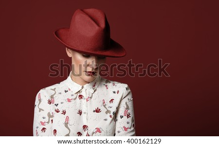 woman wears a red hat on a red background - stock photo