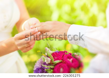 Woman wears a ring on the finger of a man - stock photo