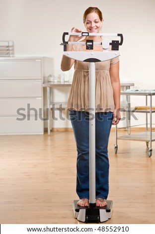 Woman weighing herself in doctor office - stock photo