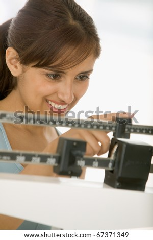 Woman weighing herself on scale - stock photo