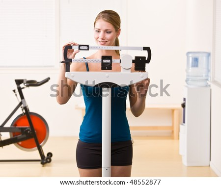 Woman weighing herself on scales in health club - stock photo