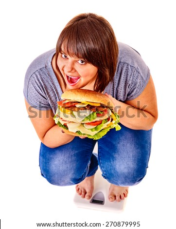 Woman weight loss on scales eating big hamburger. Isolated. - stock photo