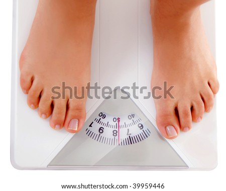Woman weighting on a scales isolated on white - stock photo