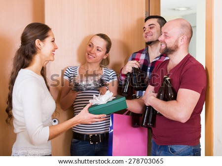 Woman welcomes joyful friends at home - stock photo
