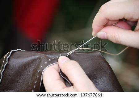 woman while sewing a dress in leather with needle and thread - stock photo