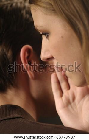 Woman whisper in ear man - stock photo