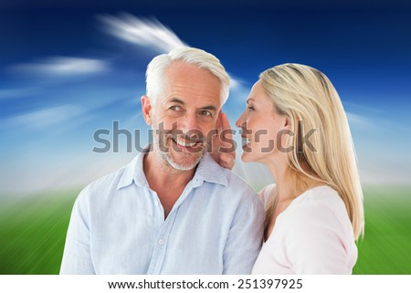 Woman whispering a secret to husband against blue sky over city - stock photo