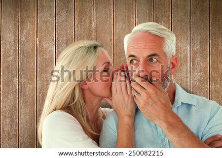 Woman whispering a secret to husband against wooden planks - stock photo