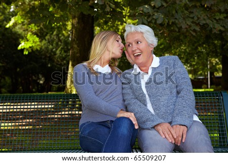 Woman whispering her deaf grandmother in the ear - stock photo