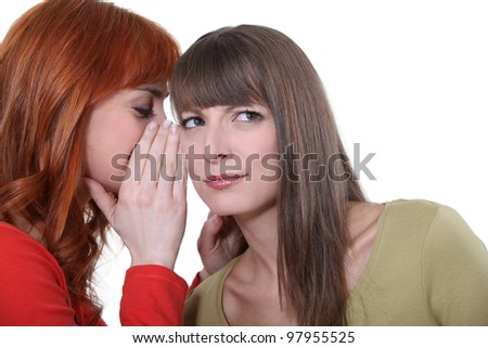Woman whispering into her friend's ear - stock photo
