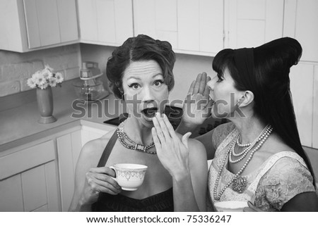 Woman whispers secret into a friend's ear - stock photo