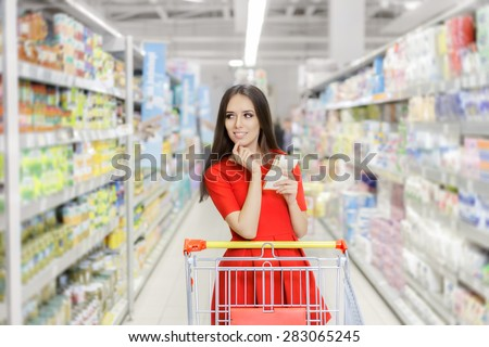Woman whit Shopping List at The Supermarket - Young girl in a market store with a shopping list thinking what to buy  - stock photo