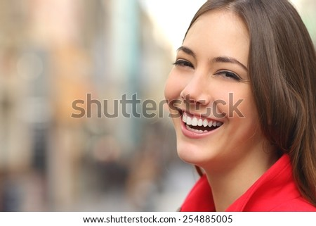 Woman white smile with a perfect teeth in the street and looking at camera - stock photo