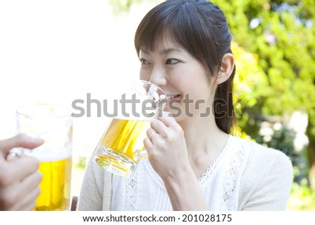Woman who drinks beer in the garden