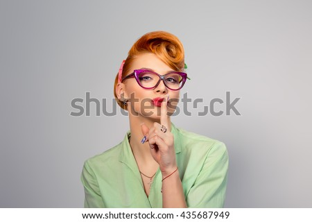 Woman wide eyed asking for silence or secrecy with finger on lips hush hand gesture grey gray background wall. Pretty girl placing fingers on lips, shhh sign symbol. Negative emotion facial expression - stock photo