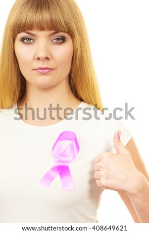 Woman wih pink cancer ribbon on chest making thumb up hand sign. Healthcare, medicine and breast cancer awareness concept. - stock photo