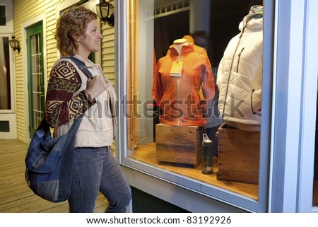 Woman window shopping for winter ski jackets at night - stock photo
