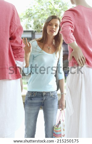 Woman window shopping, looking at mannequins in clothes shop - stock photo
