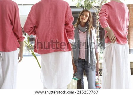 Woman window shopping, looking at three mannequins wearing pink tops and white skirts in clothes shop - stock photo