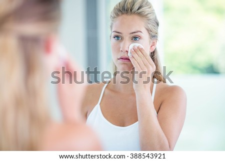 Woman wiping her face with cotton pad in the bathroom - stock photo