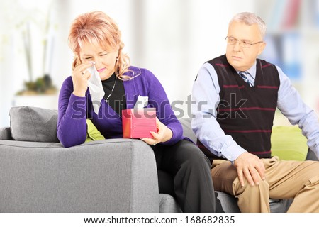 Woman wiping his eyes from crying after quarrel with her husband at home - stock photo