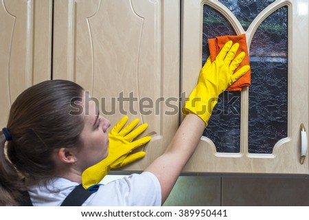 Woman wiping kitchen cupboard with rag. Housework and cleaning.