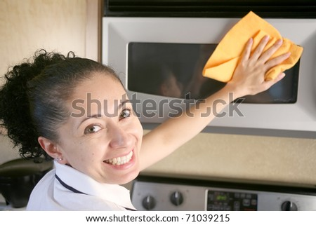 Woman wiping microwave with a rag looking back and smiling - stock photo