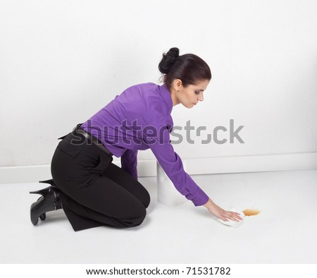 Woman wiping spilled coffee from the floor in the office