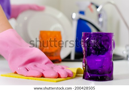 Woman wiping the kitchen counter top with a dishcloth as she places the clean glasses and crockery from washing up on the surface - stock photo