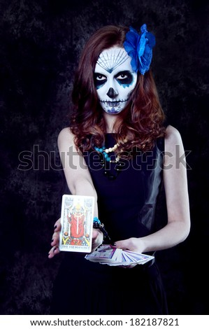 Woman witch with scary makeup with tarot cards preparing for a reading - stock photo