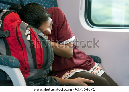 woman with a backpack sleeping in a train
