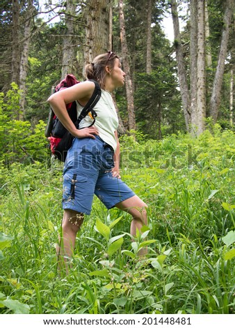 Woman with a backpack standing in a clearing on forest background