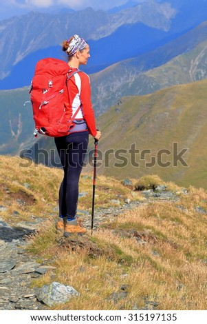Woman with a backpack standing on the side of a mountain - stock photo