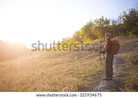 Woman with a backpack walking along the road in the woods. - stock photo