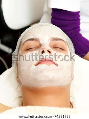 Woman with a beauty mask on her face in a salon