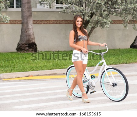 Woman with a bicycle in a pedestrian crosswalk. - stock photo