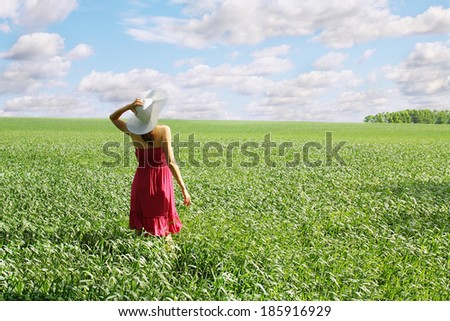 Woman with a big hat on spring field