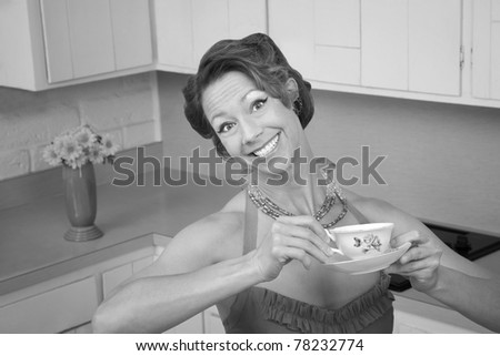 Woman with a big smile enjoys a cup of coffee in her kitchen - stock photo