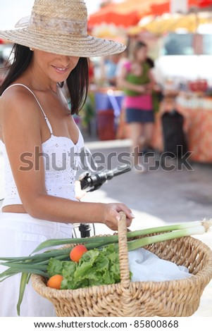 Woman with a bike and basket of market produce