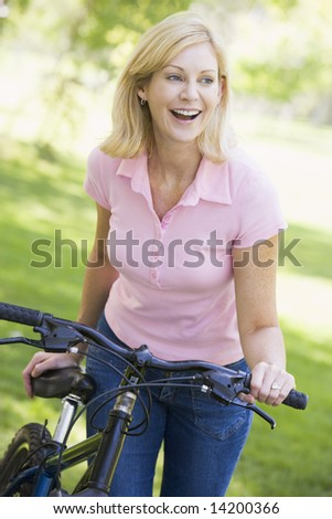 Woman with a bike outdoors smiling - stock photo