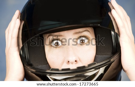 Woman with a black motrcycle helmet and surprised expression - stock photo