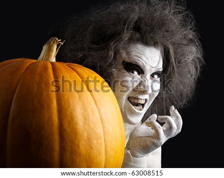 Woman with a bleached face and pumpkin. Halloween theme. - stock photo