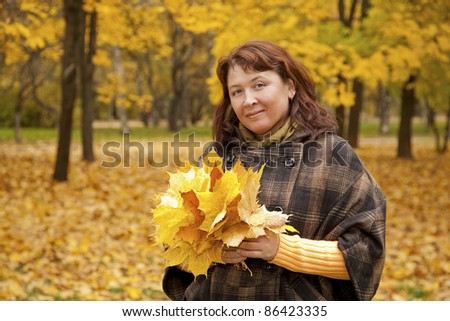 Woman with a bouquet of autumn leaves and looks at the viewer smiling - stock photo