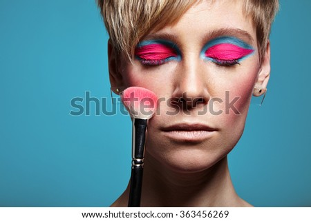woman with a bright makeup and cheek brush